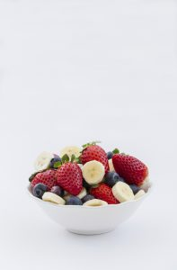 A bowl full of fresh fruit and berries including strawberries, blueberries and banana slices on an isolated white background. A bowl full of fruit smoothie ingredients.