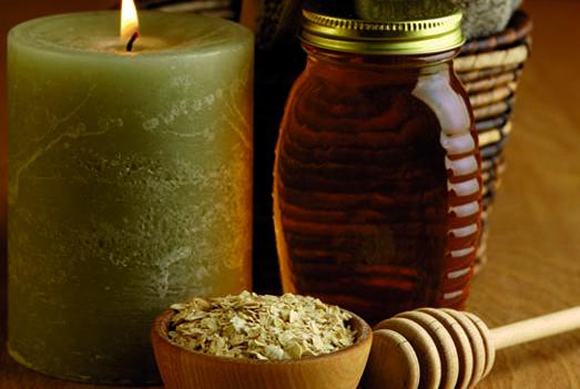 Un barattolo di miele accanto a dell'avena e a una candela accesa