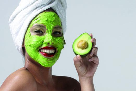 Una ragazza con una maschera all'avocado applicata al viso