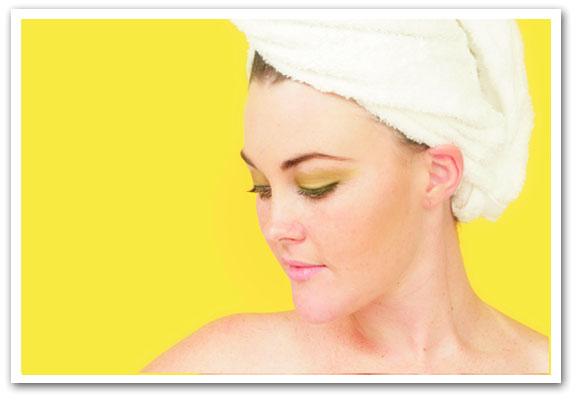 Il viso di una donna con un asciugamano tra i capelli