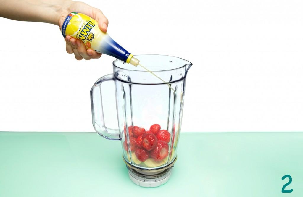 Il succo di limone Limmi viene versato nel contenitore del frullatore contenente fragole e banane tagliate a pezzetti