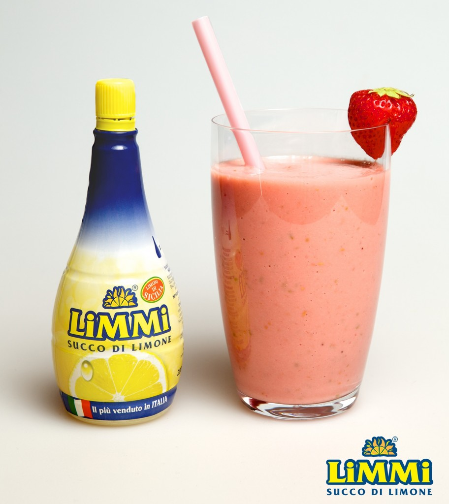 A glass of banana, strawberry and lemon smoothie next to the bottle of Limmi lemon juice